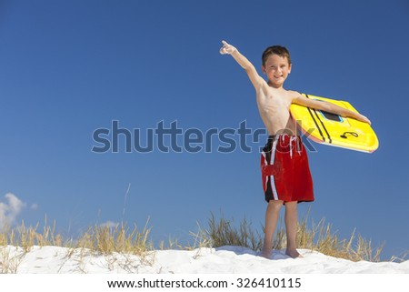 Young male boy child with yellow surfboard on a beach with bright blue sky - stock photo