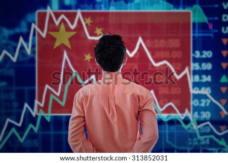 Young male broker looking at a stock market of china with declining arrows - stock photo