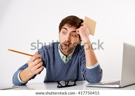 Young male business employee is bored in front of his computer looking away. Realistic and authentic situation at every office. - stock photo