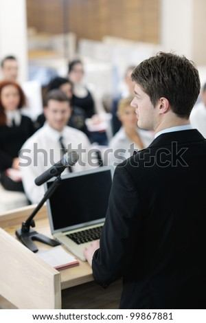 young  male business man giving a presentation at a  meeting seminar at modern conference room  on a table board - stock photo