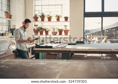 Young male business owner standing in his studio workshop checking figures and stock on his clipboard on a sunny afternoon - stock photo