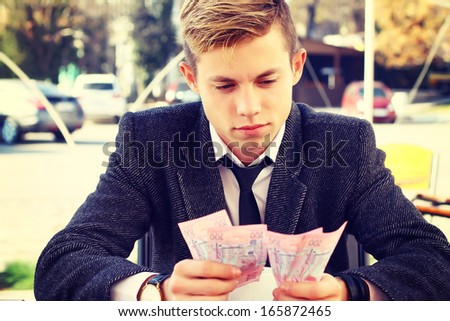 young male businessman counts money - stock photo