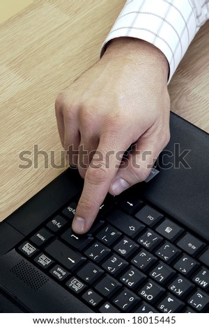 Young male businessman pressing enter - stock photo