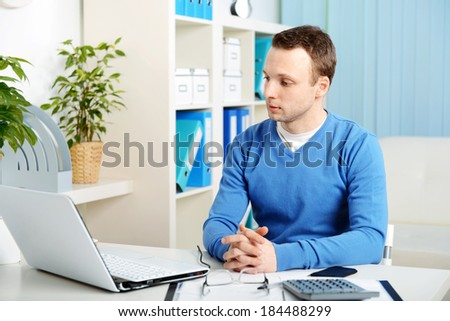 young male businessman sitting in office and working