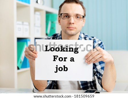 "young male businessman sitting in office with a sign ""looking for job"", focus on hands - stock photo"
