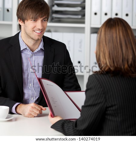 Young male candidate looking at businesswoman taking interview at office desk - stock photo