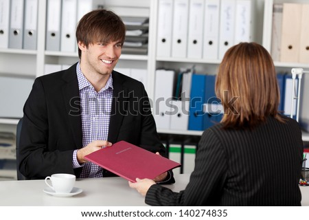 Young male candidate looking at businesswoman taking interview in office - stock photo