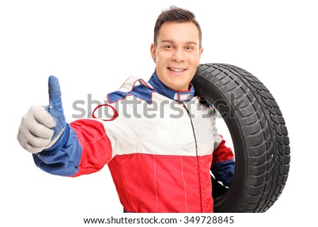 Young male car racer holding a tire and giving a thumb up isolated on white background - stock photo
