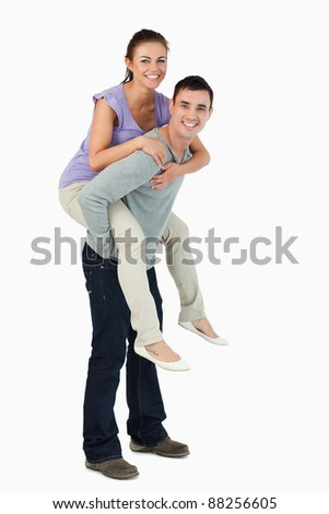 Young male carrying his girlfriend piggyback against a white background
