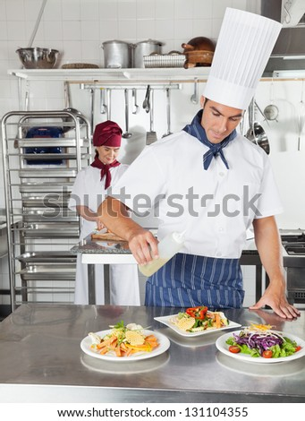 Young male chef adding oil on dish with colleague working in background - stock photo