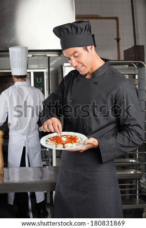 Young male chef garnishing dish with colleague in background
