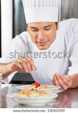 Young male chef sprinkling spices on dish in commercial kitchen