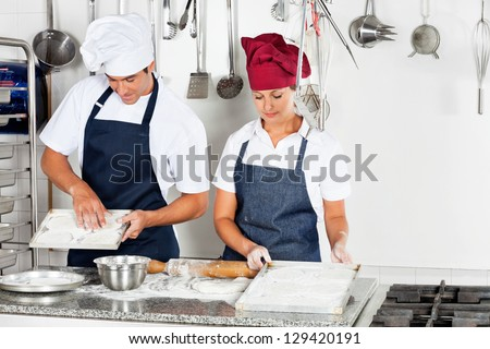 Young male chef with female colleague baking in commercial kitchen - stock photo
