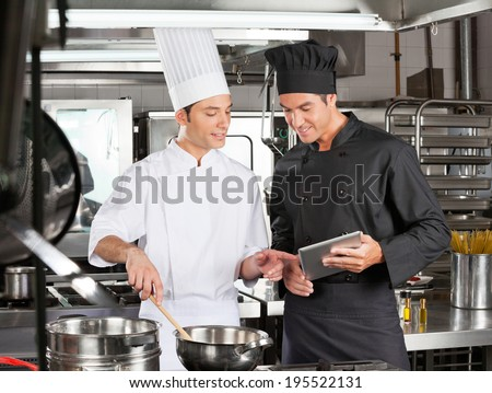 Young male chefs looking at digital tablet while preparing food in restaurant kitchen - stock photo