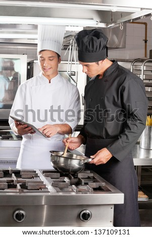 Young male chefs with digital tablet preparing food in restaurant kitchen
