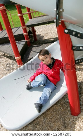 young male child playing on the slide at a playground