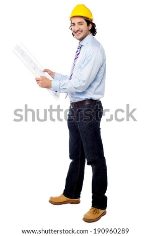 Young male civil engineer with construction plan - stock photo