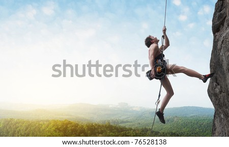 Young male climber hanging by a cliff on wide alley background - stock photo