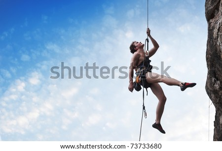 Young male climber hanging on a rope and looking to somewhere on blue cloudy sky background - stock photo