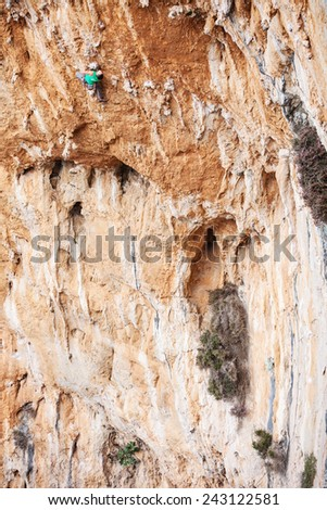 Young male climber on a face of a cliff
