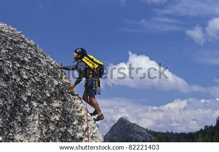Young male climber struggles up  a challenging rock wall. - stock photo