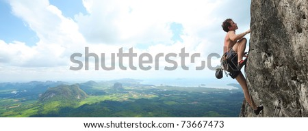 Young male climbing on a cliff on wide alley background - stock photo