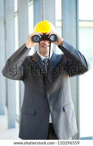 young male construction manager using binoculars - stock photo