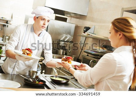 young male cook chef in white uniform gives to waitress plates with prepared meal in commercial kitchen - stock photo