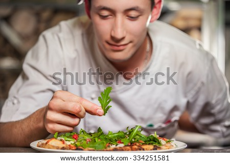 young male cook preparing delicious appetizer with herbs on white plate - stock photo