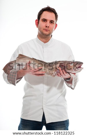 Young male cook with white jacket holding a big fish isolated on white. - stock photo