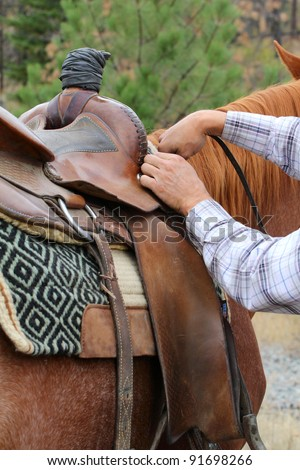 Young male cowboy adjusting the saddle on his horse - stock photo