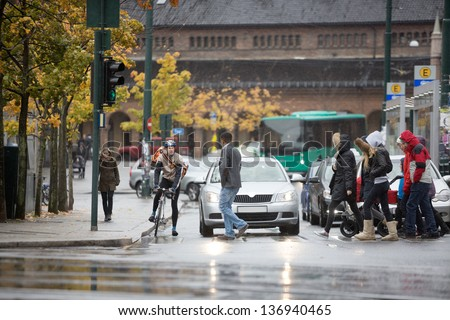 Young male cyclist along with other vehicles waiting for commuters to cross the street - stock photo