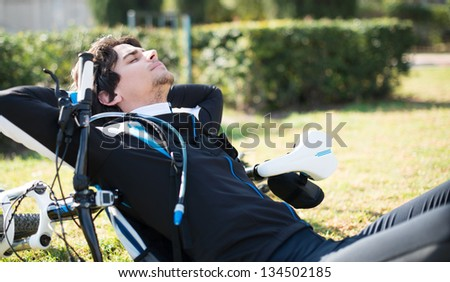 Young Male Cyclist Relaxing; Outdoors - stock photo