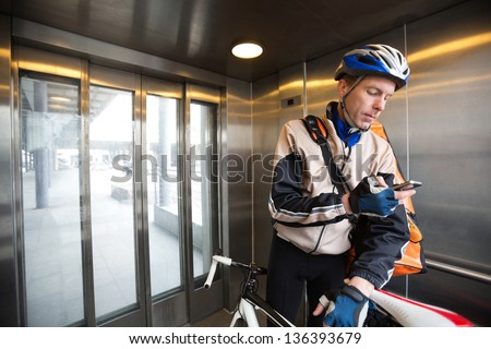 Young male cyclist with courier delivery bag using mobile phone in an elevator - stock photo