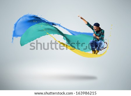 young male dancer jumping surrounded by splashes of paint - stock photo