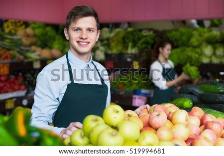 Young male dealer lays out the apples on the counter and smiling
