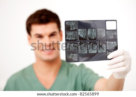 Young male dentist holding an x-ray, shallow depth of field - focus on x-ray - stock photo
