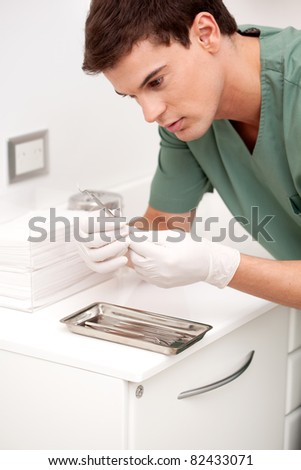 Young male dentist inspecting sterile dentistry tool - stock photo