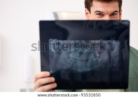 Young male dentist looking at an x-ray, eyes visiable over top - stock photo