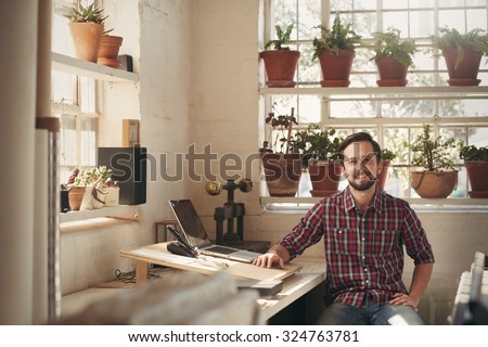 Young male designer sitting comfortably in his office space in his studio which has beautiful natural light and many plants - stock photo