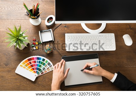 Young Male Designer Using Digital Graphic Tablet With Stylus At Desk - stock photo