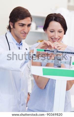 Young male doctor adjusting scale for his patient