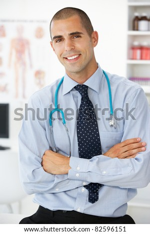 Young male doctor in consulting room - stock photo
