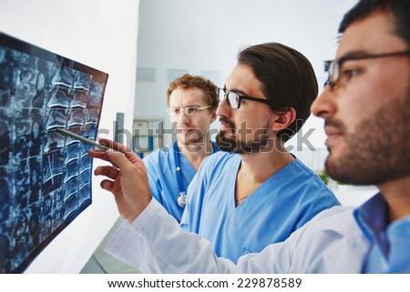 Young male doctor pointing at x-ray and discussing it with colleagues