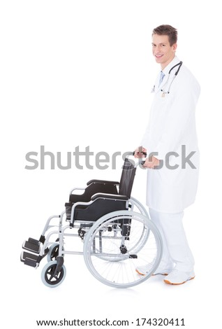 Young Male Doctor Pushing Wheelchair Over White Background