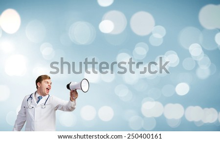Young male doctor screaming in megaphone emotionally - stock photo