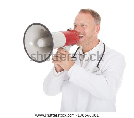 Young male doctor screaming into megaphone over white background
