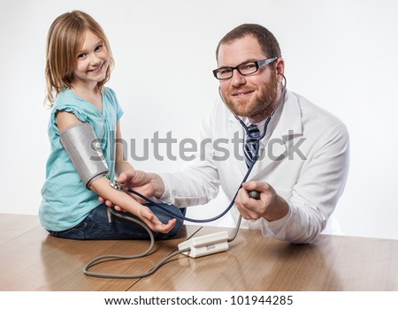 Young male doctor smiling while administering blood pressure examination on little white girl in blue shirt