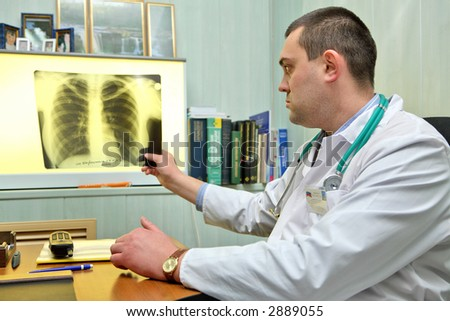 Young male doctor throwing a look to a chest x-ray image - stock photo