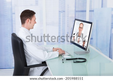 Young male doctor video conferencing with colleagues through computer in hospital - stock photo